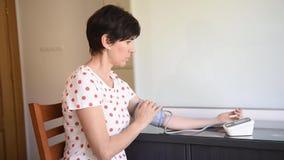 Donna di mezza età che misura la sua propria pressione sanguigna con un dispositivo elettronico di misura di pressione sanguigna video d archivio