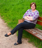 Donna di mezza età che si rilassa su un banco di parco Immagine Stock Libera da Diritti