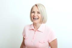 Donna di mezza età sorridente amichevole su fondo bianco Fotografie Stock Libere da Diritti