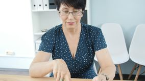 Donna di mezza età in ufficio che lavora alla compressa digitale archivi video