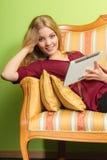 Donna di modo che mette su sofà con la compressa del pc Immagine Stock