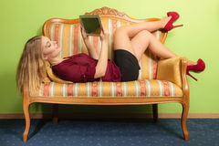 Donna di modo che mette su sofà con la compressa del pc Fotografia Stock
