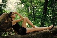 Donna di modo nella posa alla moda del vestito sul tronco di albero Modello di moda con trucco e capelli ricci lunghi sulla natur fotografie stock