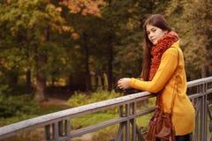 Donna di modo sul ponte nel parco di autunno Fotografie Stock