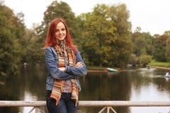 Donna di modo sul ponte nel parco di autunno Fotografia Stock