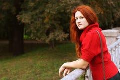 Donna di modo sul ponte nel parco di autunno Immagini Stock
