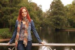 Donna di modo sul ponte nel parco di autunno Fotografie Stock Libere da Diritti