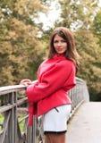 Donna di modo sul ponte nel parco di autunno Immagini Stock Libere da Diritti
