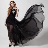Donna di modo in vestito nero d'ondeggiamento Priorità bassa bianca Immagine Stock Libera da Diritti