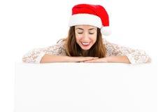 Donna di Natale che guarda dall'alto in basso un'insegna di pubblicità immagine stock