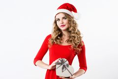 Donna di Natale in un vestito ed in un cappello rossi di Santa con un contenitore di regalo Fotografie Stock