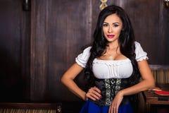 Donna di Oktoberfest che porta un dirndl bavarese tradizionale del vestito che posa alla barra immagine stock