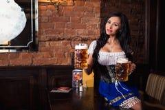 Donna di Oktoberfest che porta un dirndl bavarese tradizionale del vestito che posa con una tazza di birra alla barra fotografie stock
