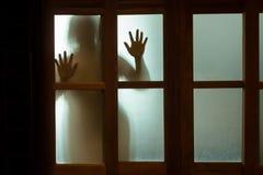 Donna di orrore dietro il vetro di finestra in bianco e nero blurry fotografia stock