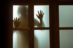 Donna di orrore dietro il vetro di finestra in bianco e nero blurry immagine stock libera da diritti