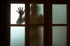 Donna di orrore dietro il vetro di finestra in bianco e nero blurry fotografia stock libera da diritti