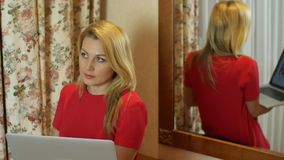 Donna di pensiero che considera computer portatile che sta di nuovo allo specchio archivi video