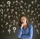 Donna di pensiero di affari con i punti interrogativi del gesso Immagine Stock