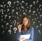 Donna di pensiero di affari con i punti interrogativi del gesso Fotografia Stock
