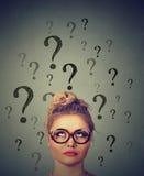 Donna di pensiero di affari con i vetri che cerca la testa di cui sopra di molti punti interrogativi Immagini Stock
