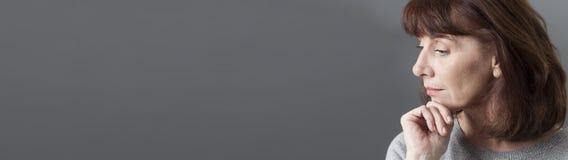 Donna di pensiero 50s che medita su profilo, panorama lungo grigio Fotografia Stock