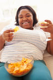 Donna di peso eccessivo a casa che mangia Chips And Drinking Wine Immagine Stock Libera da Diritti