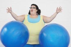 Donna di peso eccessivo che cade due palle di esercizio fotografia stock