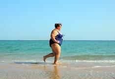 Donna di peso eccessivo che funziona sulla spiaggia Fotografie Stock Libere da Diritti