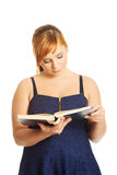 Donna di peso eccessivo che legge un libro fotografia stock libera da diritti