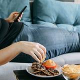 Donna di peso eccessivo che mette su sofà che mangia alimento zuccherato fotografia stock libera da diritti