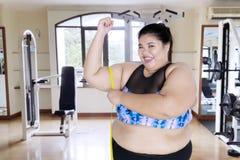 Donna di peso eccessivo che misura il suo bicipite immagini stock libere da diritti