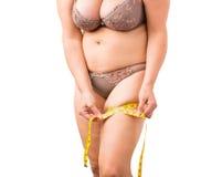 Donna di peso eccessivo che misura la sua anca fotografie stock libere da diritti