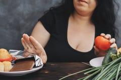 Donna di peso eccessivo che rifiuta la barra di cioccolato fotografia stock libera da diritti
