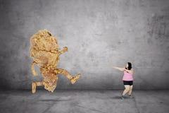 Donna di peso eccessivo che sfugge da un pollo fritto Fotografia Stock