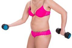 Donna di peso eccessivo che si esercita con le teste di legno fotografia stock libera da diritti