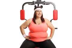 Donna di peso eccessivo che si siede su una macchina d'esercitazione di forma fisica fotografie stock