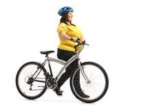 Donna di peso eccessivo che spinge una bicicletta fotografia stock