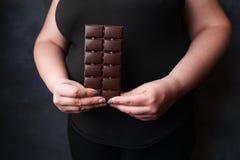 Donna di peso eccessivo con la barra di cioccolato Perdita di peso immagine stock libera da diritti