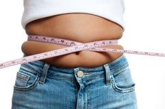 Donna di peso eccessivo con la misura di nastro intorno alla vita immagini stock