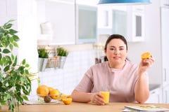 Donna di peso eccessivo con vetro di succo e dell'arancia freschi in cucina fotografie stock libere da diritti