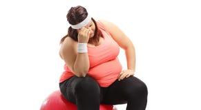 Donna di peso eccessivo emozionale che si siede su una palla di esercizio fotografia stock libera da diritti