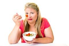 Donna di peso eccessivo facente smorfie con la ciotola di insalata fotografia stock
