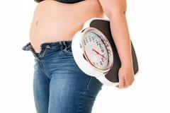 Donna di peso eccessivo grassa che porta una bilancia pesa-persone Fotografia Stock