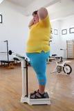 Donna di peso eccessivo impressionata sulle scale in palestra fotografia stock