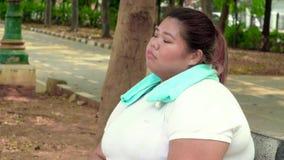 Donna di peso eccessivo triste che si siede al parco video d archivio