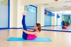 Donna di Pilates che allunga allenamento di esercizio alla palestra Immagine Stock
