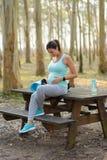 Donna di Pregnat che prende un resto di allenamento di forma fisica Immagine Stock