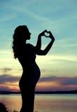 Donna di Prgenant che fa il segno del cuore Fotografia Stock