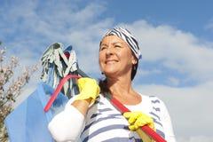 Donna di pulizie di primavera esterna Fotografia Stock