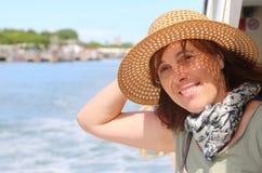 Donna di quaranta anni sveglia con il cappello di paglia immagini stock libere da diritti